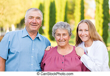 Elderly care - Happy elderly couple with their carer in the...