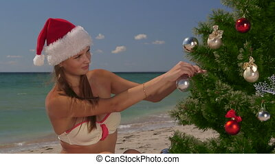 Girl in Santa hat decorates a Christmas tree on tropical beach