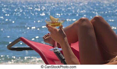 Girl with cocktail enjoying summer vacation on tropical beach resort