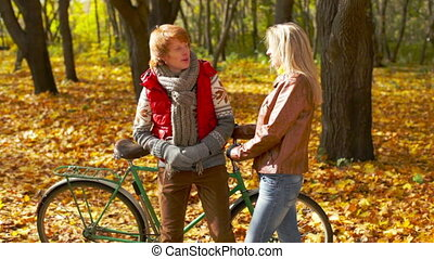 Autumn Springs - Girl and boy flirting in autumnal park...