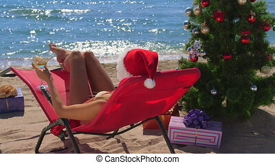 Girl in red Santa hat celebrating Christmas on sandy beach -...