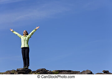 Woman Celebrating Achievement At The Top Of A Mountain - A...