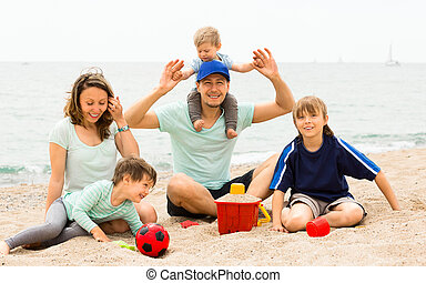 Portrait of smiling parents and their children on sand