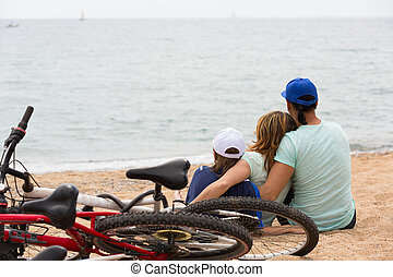 Family with bicycles on beach - Couple with teenager son...