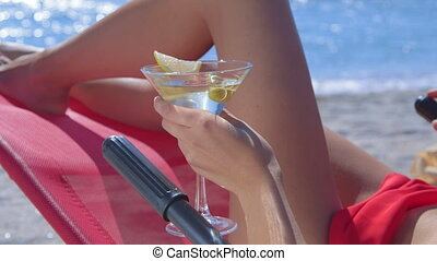 Female hand holding martini with olives on tropical beach...