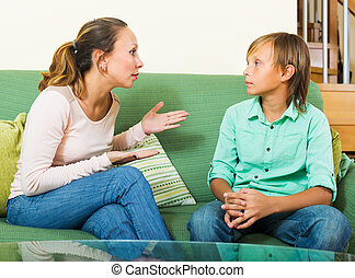 Serious mother and teen boy talking in home - Serious...