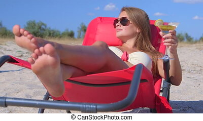 Young woman lying on beach lounger with cocktail enjoying...