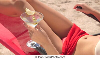 Young woman holding martini cocktail with olives on summer...