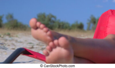 Pretty young woman with cocktail glass sunbathing on summer beach