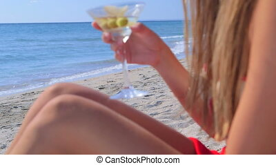 Young woman drinking martini cocktail on the summer sandy beach