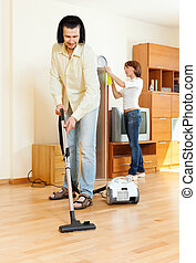 couple cleaning with vacuum cleaner in living room