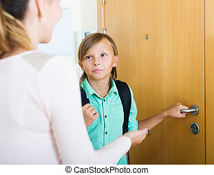Teenager and mother staying near flat entrance - Teenager...