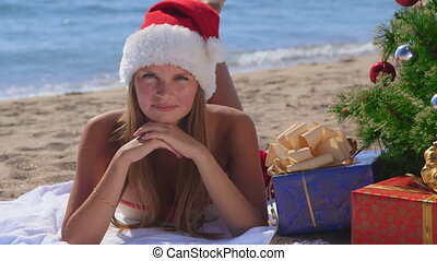 Smiling pretty woman with gifts under decorated Christmas tree on tropical beach