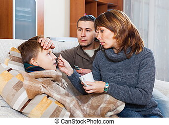 Parents giving pills to boy - Loving parents giving pills to...