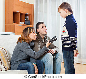 Parents with belt scolding teenager boy at home