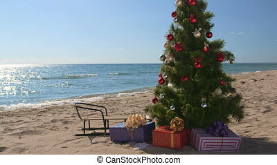 Decorated Christmas tree with gift boxes on a sandy beach