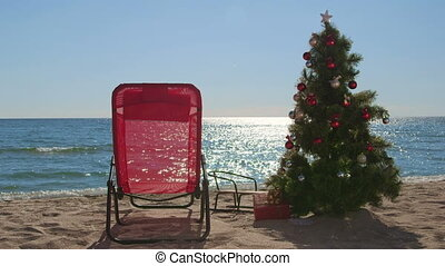 Lounge chair and Christmas tree with gift boxes on sandy...