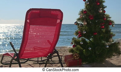 Lounge chair and Christmas tree with gift boxes on sandy beach