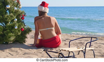 Girl in Santa hat near Christmas tree on the beach rear view