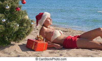 Girl in Santa hat enjoying Christmas vacation time on beach...