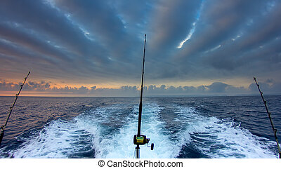 Boat fishing rods over a beautiful cloudy seascape