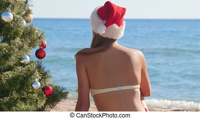 Girl in Santa hat near Christmas tree on the beach rear view...