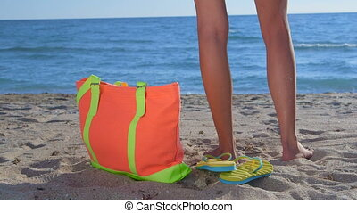Colorful bag and flip-flops on sandy beach bikini woman in...