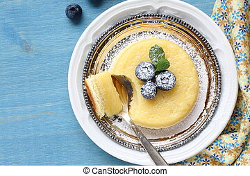 Lemon delicious pudding cake served with berries - Lemon...