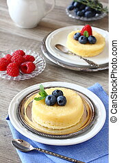 Delicious lemon pudding cake served with berries - Lemon...
