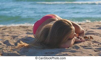 Young girl in pink bikini lying on the beach by sea
