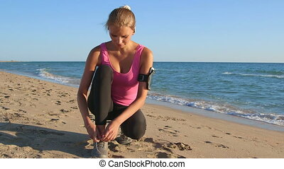 Fitness girl lacing running shoes before jogging on beach