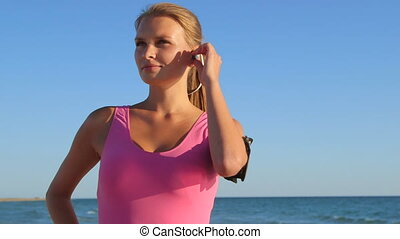 Fitness athletic girl using sport wireless headset while...