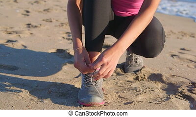 Fitness athletic girl lacing sport shoes before start...