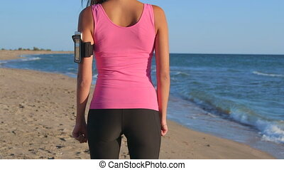 Fitness woman jogging on beach listening music in earphones...
