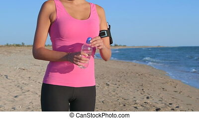 Fitness sporty woman training outdoors taking break to drink...