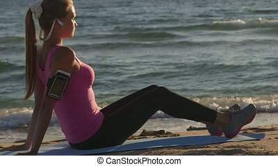 Fitness athletic girl exercising on the beach at sunset