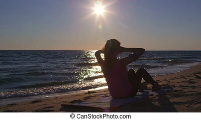 Fitness athletic woman doing abdominal crunch during workout on the beach at sunset