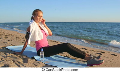 Fitness sporty woman in wireless headset relaxing after...