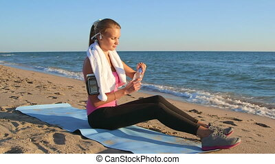 Fitness sporty woman in wireless headset relaxing after workout
