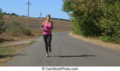 Fitness running woman jogging during outdoor workout along country road
