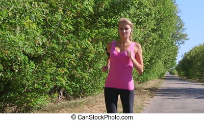 Fitness athletic girl jogging along the road during outdoor...