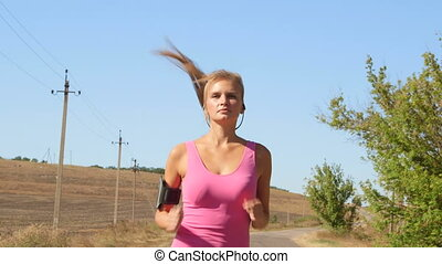 Fitness woman runner in headset listening music jogging on...