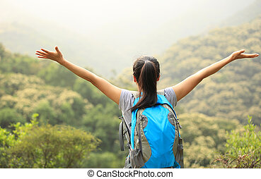 woman hiker open arms to mountains