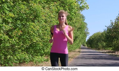 Fit girl jogging on the road during outdoor workout