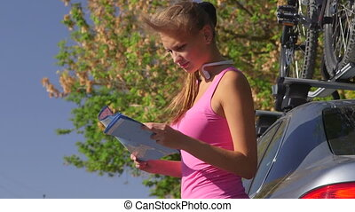 Young fit woman driver stand near car and look on map for directions