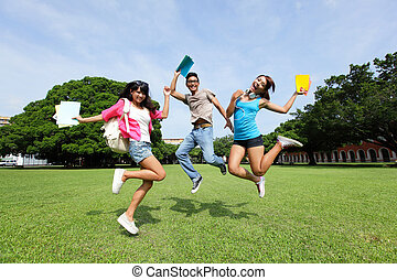 Happy College students jump and smile to you on campus lawn,...