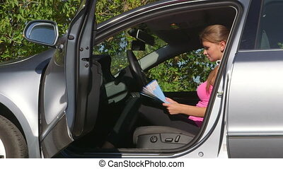 Young woman driver traveling by car looking at map