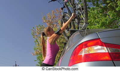 Woman cyclist fixing bicycle on roof of car after workout