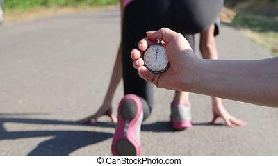 Stopwatch in hand  female runner athlete feet running on road