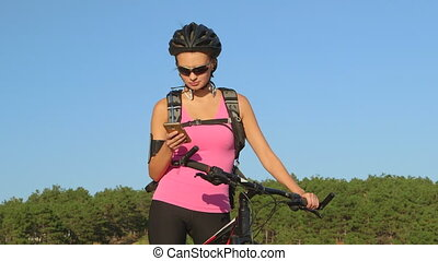 Young woman cyclist on mountain bike tracks cycling workout on smart phone